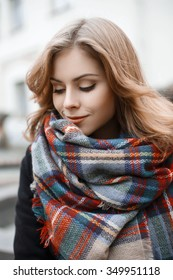 Cute young woman in trendy knitted scarf and black coat in autumn day
