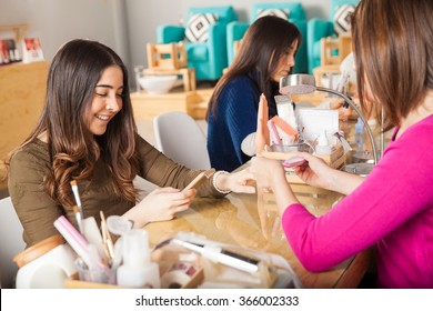 Cute young woman using her smartphone while getting a manicure at a nail salon