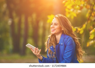 Cute young woman using smartphone in the park with autumn season colors.
