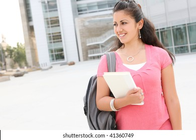 A cute young woman walking to class  on  college campus