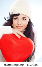 Cute young woman wearing warm winter clothing and holding heart posing in studio