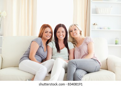 Cute young women sitting on a sofa in a living room