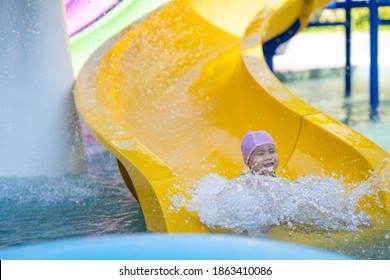 Cutel little girl playing waterslide at waterpark.