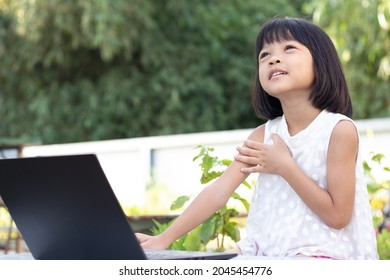 A cute-looking Asian kindergarten girl  is studying online on a black laptop in her backyard. left hand raised on chest. Look upward in a pose that uses the thoughts and imaginations of the class.