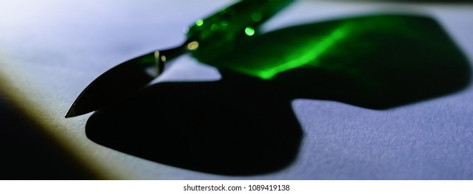Cuticle knife reflecting bright green color through its emerald handle