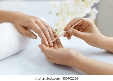 Cuticle Remover. Closeup Of Woman Hands Receiving Manicure And Nail Care Procedure. Close-up Manicurist Pushing Cuticles On Female Nails With Wooden Stick For Cuticle In Beauty Salon. High Resolution