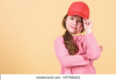 Cutie in cap. Stylish accessory. Kids fashion. Feeling confident with this cap. Girl cute child wear cap or snapback hat beige background. Little girl wearing bright baseball cap. Modern fashion.
