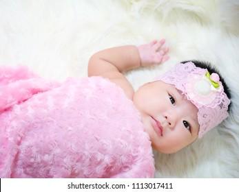 Cutie newborn baby on white fabric background.