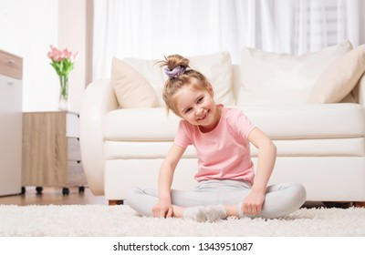 Cutie preteen kid sitting in relaxing yoga pose in bright room