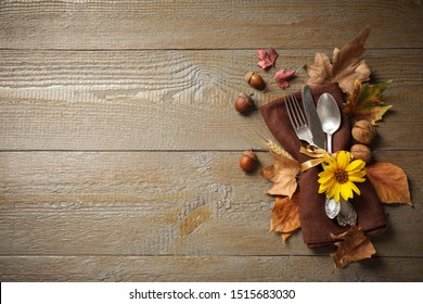 Cutlery and autumn decorations on wooden background, flat lay with space for text. Happy Thanksgiving day