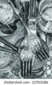 Cutlery and glasses being washed with water and detergent