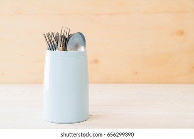 Cutlery holder spoon and fork on wood background