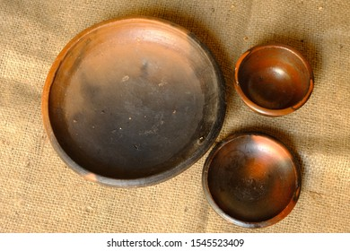 cutlery made of earthenware on burlap sacks. earthenware made of clay which is formed and burned in the manufacturing process. earthenware plates and bowls. Indonesian traditional tools.