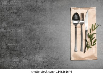 Cutlery and napkin on gray background, top view. Table setting