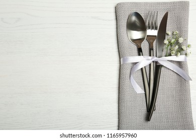 Cutlery and napkin on light wooden background, top view. Table setting