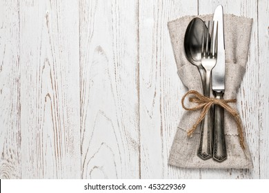 Cutlery is in a napkin wrapped on an old table