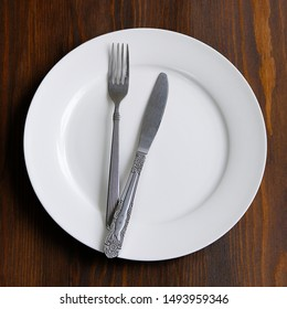 Cutlery on an empty white plate, on a wooden background. Fork and spoon in a bowl. The concept of food. Copy the space for the text.