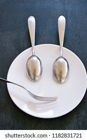 Cutlery on a plate forms a face - concept with cutlery like spoon and fork as a face on a plate against a dark background