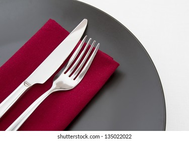 Cutlery on red napkin with black plate