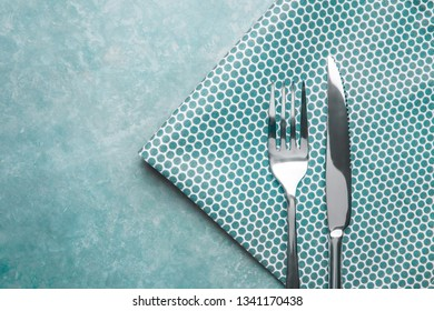 Cutlery on the table. Fork and knife with napkin. Top view.