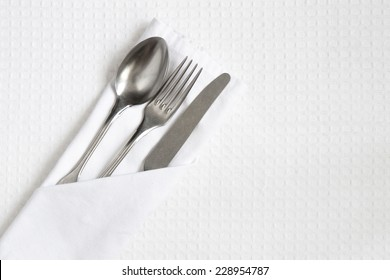 Cutlery on white linen with space for text