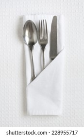 Cutlery on white linen as a table place setting