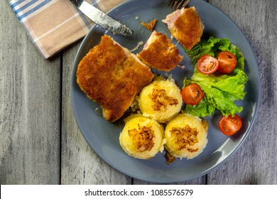 Cutlet cordon bleu with pork ham served with boiled potato and salad on a plate. Top view.