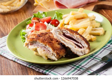 Cutlet Cordon Bleu with pork loin served with French fries and salad on a plate