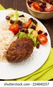 cutlet with rice and vegetable salad on a plate