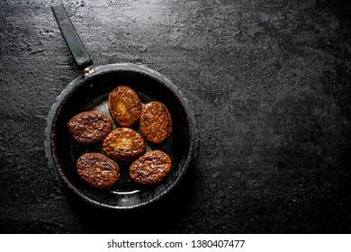 Cutlets in an old pan. On black rustic background