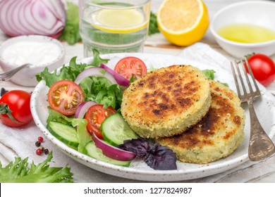 Cutlets (patties ) from white fish (Pollock, cod, perch, pike) in a Plate with lettuce, tomato and cucumber salad. Healthy gourmet dinner. Selective focus