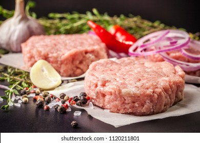 Cutlets from raw minced pork, lamb, veal or beef on parchment. Nearby spices and vegetables. On a black and wooden background. Copy space
