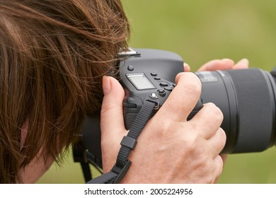A cut-off image of a woman with a camera. She looks into the viewfinder, and her hand presses the shutter release of the camera. Close-up.