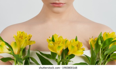 A cut-off image of a young woman: the cleavage area framed by yellow flowers.