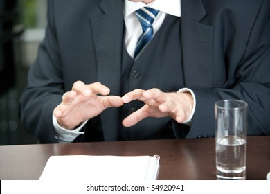 cutout af a male torso in a three-parted gray suit with his hands gesticulating over the desk