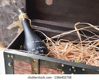 cutout and close-up of an old wooden box opened. in the corner is a dark wine or bottle of champagne, without original label, set on a light straw. It is painted and labeled by hand.