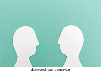 Cutout human heads in front of each other during dialogue against blue background
