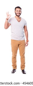 """Cutout latino man making """"OK"""" gesture. Looks handsome and smiling. Isolated on white background. Full length."""