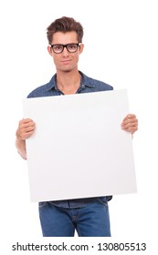 cutout picture of a casual young man holding a small panel with both his hands and smiling to the camera. isolated on a white background