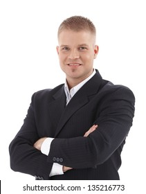 Cutout portrait of smiling businessman standing with arms folded, looking at camera.