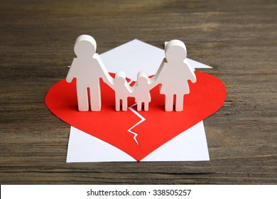 Cutout silhouette of a family split apart on a paper heart, divorce concept
