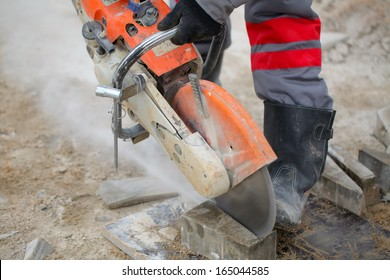 cuts concrete tile.Profile on the blade of an asphalt or concrete cutter and workers boots .Construction worker using a concrete saw, cutting stones in a cloud of concrete dust for creating a track.