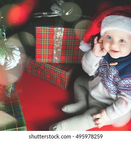 Cutte baby looking at camera, Cristmas night. Dressed at Santa hat. Christmas family celebration