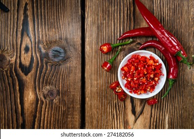 Cutted red Chilis in a bowl (close-up shot) on wooden background