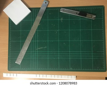 cutter knife, ruller and notepad on green cutting mat
