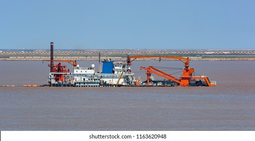 Cutter suction dredger at work of land reclamation for new ports positioned on spuds as anchors and discharge dredged soil through a floating pipeline. Shanghai, China