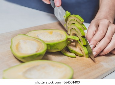 Cutting avocado on light wooden desk