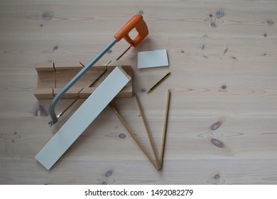 Cutting baseboards using a saw and miter box, on a wooden floor.