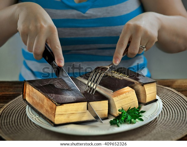 Cutting up a Bible for eating at dinner.