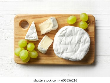 Cutting board of camembert cheese and grapes on white wooden background. From top view